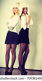 Clothing people fashion concept. Full length of two ladies in winter outfit. Blonde woman together with mulatto girl, wearing white warm clothes.