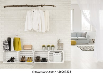 Clothing rack hanging on a wall, shoe racks made from wooden boxes, light room in the background