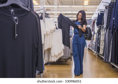 Clothing, sale and advertise concept - Asian woman choosing black business suit and shirt at shopping center or supermarket. (lens blur effect)