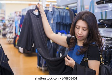 Clothing, Sale and Advertise concept - Asian woman choosing Black T-Shirt at shopping center or supermarket. (lens blur effect)