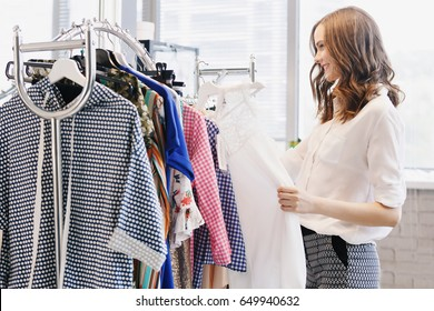 Clothing stylist young woman chooses clothes in a store