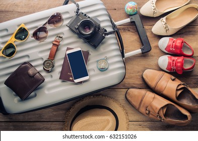 Clothing traveler's Passport, wallet, glasses, smart phone devices, on a wooden floor in the luggage ready to travel with family