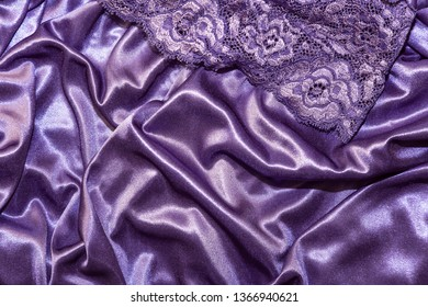 Clothing, underwear. Abstract elegant silk satin purple background with highlights with a soft fabric texture with a lace stocking element