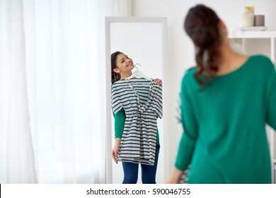 clothing, wardrobe, fashion, style and people concept - happy woman with shirt looking to mirror at home