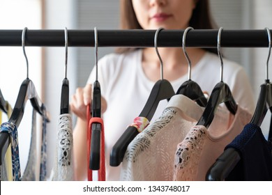 Clothing wardrobe fashion trend concept. close up focus asian female hand choosing holding hangers on cloth dress in the morning in bedroom. unrecognized elegant woman smiling picking outfit at home.