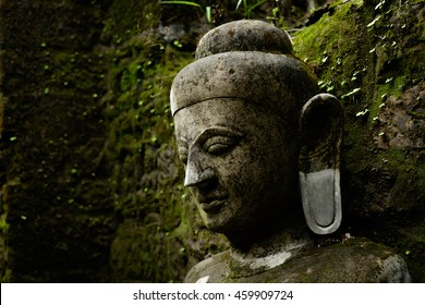 Cloth-up of Buddha statue covered by moss in ruins of Kothaung Paya temple in Mrauk-U city, Myanmar