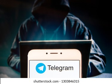 Cloud based instant messaging Telegram logo is seen on an Android mobile device with a figure of hacker in the background.