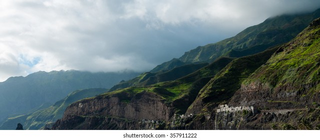Cloud black rock stone coastline with houses and green hill in cape verde island