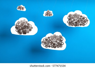 Cloud computing concept with cogs and gears showing how cloud computing works. Blue sky background and cardboard cutout clouds