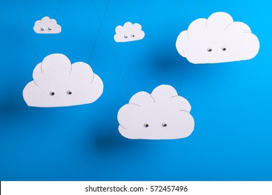Cloud computing concept with white cardboard cutout cute clouds with eyes hanging in front of a sky blue background.