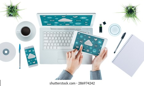 Cloud computing and multiplatform concept, user interface on laptop, tablet and smartphone, female hands touching an icon