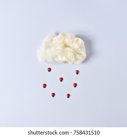 Cloud from Cotton Candy with Ladybug Rain on Blue Background. Minimal Nature Concept. Flat Lay.