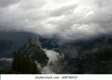 Cloud covered mountains in Yosemite National Park, California, USA, with partially visible visible peaks especially Half Dome, forests and steep cliffs.