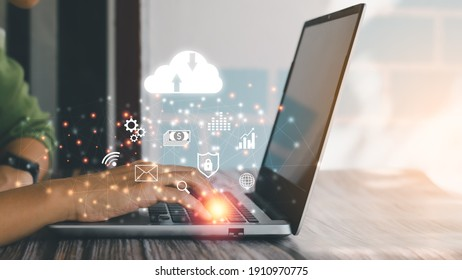 Cloud data storage concept. Human hand using laptop with virtual popup icon of cloud computing, wifi, money, data and lock security Communication of business and financial.