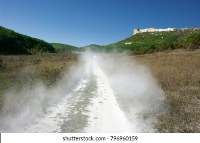 Cloud of dust as track of off road vehicle moving on country road.