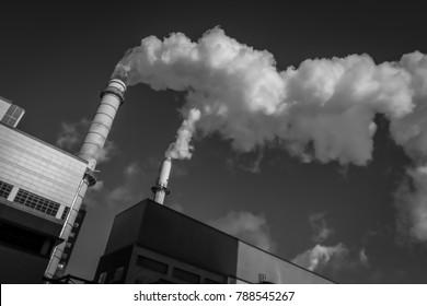 Cloud factory, smokestacks, billowing smoke against bright blue sky.