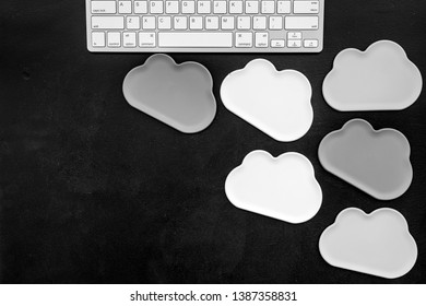 Cloud figures and keyboard for cloud storage on black background top view mockup