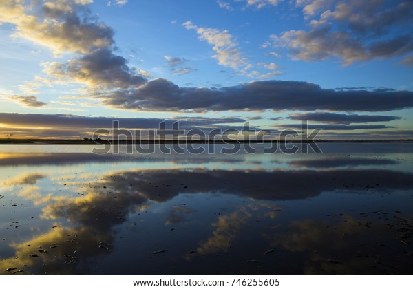Cloud formations at sunset reflected in the mirror smooth waters of Lake Tyrrell, a  shallow salt lake near the tiny town of Sea Lake in North West Victoria, Australia.