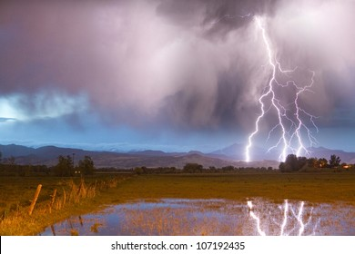 Cloud to ground lightning bolts striking the front range foothills of the Colorado Rocky Mountains in Boulder County.  A view of Mount Meeker 13,911' and Longs Peak 14,256' in the distance.