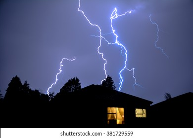 Cloud to Ground Urban Lightning, Lighting Up House Rooftops Silhouetting in foreground.