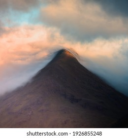 Cloud inversion in Glencoe, Scottish Highlands at sunrise.Clouds rolling over mountain peak lit by morning sunlight.Painterly landscape scenery.Fine art photographic print.