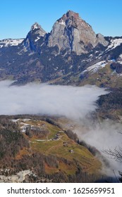 A cloud inversion sits in the Schwyz valley, Grosser (large) Mythen and Kleiner (little) Mythen peaks dominate the skyline. Green Meadows and farm buildings in the fore ground