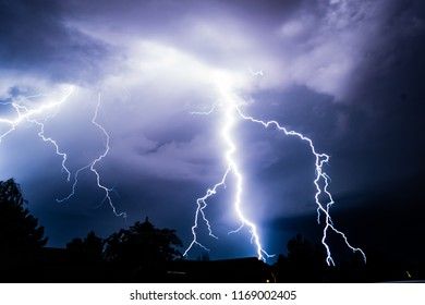 cloud lightning at night and fork lightning ground strikes. white lightning with some additional colors.