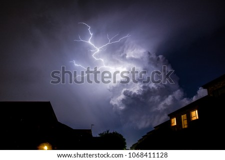 Cloud to cloud lightning strike above roof tops