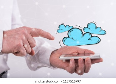 Cloud networking concept above a smartphone held by a man