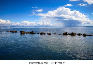 Cloud on the sea and stones in the water, seascape near the coast of Corfu island in Greece