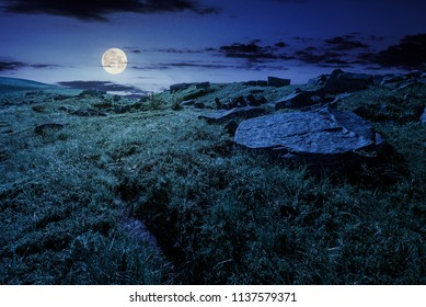 cloud over the grassy hillside with rocks at night in full moon light. path uphill in to the sky. lovely summer scenery. tracking and hiking activity background