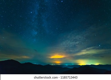 The cloud stream above mountains with stars. evening night time