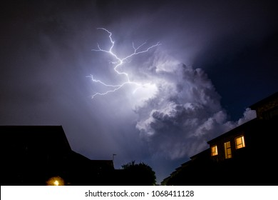 Cloud to Cloud Urban Lightning, Lighting Up House Rooftops Silhouetting in foreground.