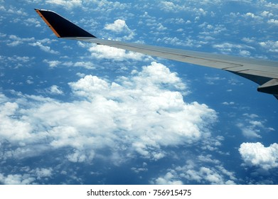 cloud & wing seen through window of aircraft