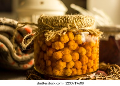 Cloudberry berry in a glass jar. Cloudberry jam. Northern berry of yellow color in a glass jar. Juicy ripe cloudberry