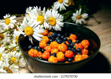 Cloudberry & blueberry (bilberry, whortleberry, huckleberry, blaeberry) in bowl with white flowers daisies. Cloudberry berry mix. Wild chamaemorus berries organic on wooden background in summer day