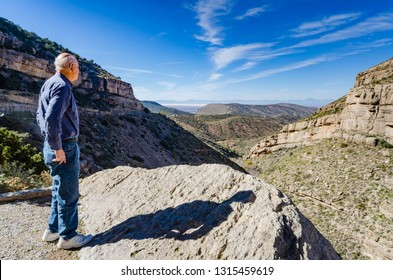 Cloudburst, NM / USA - 11-16-2014: Senior male looks out on amazing vista of Fresnal Canyon at Lincoln National Forest in New Mexico. Fresnal Canyon at Lincoln National Forest in New Mexico.