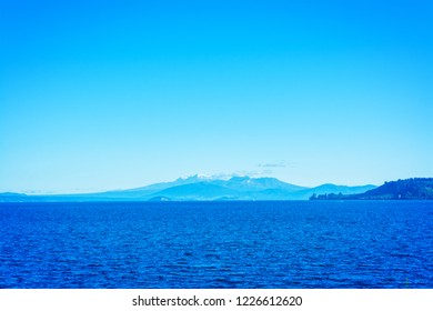 Cloudless say over volcanic cones of Ruapehu towering over great lake of Taupo. North Island Volcanic Plateau, New Zealand