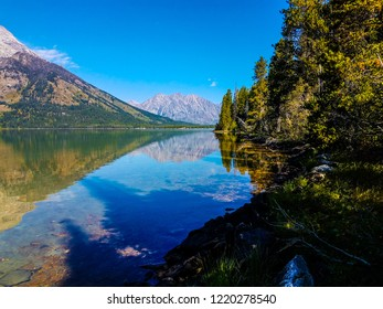 The cloudless sky provides a striking azure reflection onto Leigh Lake in Grand Teton NP in Wyoming. A mirror image of the mountain is also present. Shadows from trees on shore fall on the lake.