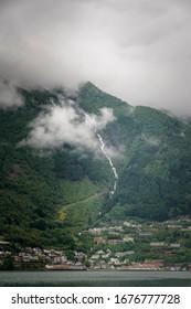 Clouds above Odda town below big waterfall Norway