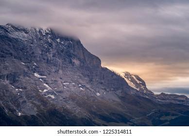 Clouds above the Schreckhorn and Eiger mountain peaks at sunset in the alpine region of Grindelwald, Switzerland.