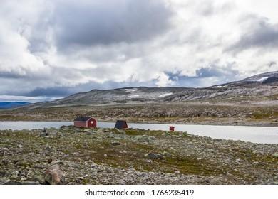Wolken über den Holzhütten an der Bergstraße bei Aurlandsvangen in Norwegen