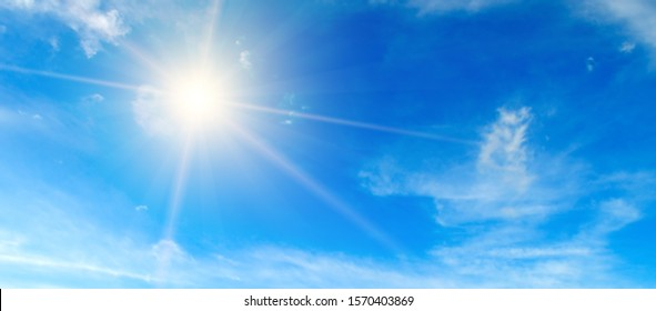 Clouds in the blue sky. Bright midday sun illuminates the space. Wide photo .
