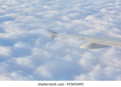 Clouds in blue sky in high view trough airplane window