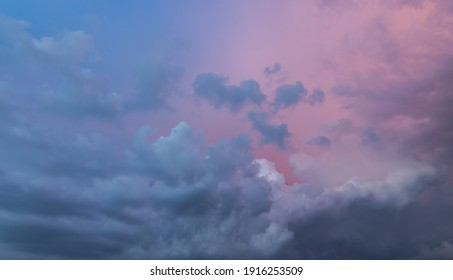 Clouds in the blue sky at sunset or dawn backlit by the sun. Place for text and design. Heaven and clouds with copy space. Looking up in the sky. Background picture. View into infinity