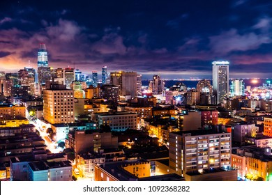 Clouds break over San Francisco , California Skyline Cityscape at night with amazing long exposure streets leading up to downtown skyscrapers and Nightscape night life in the crowded city on the slope