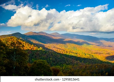 The clouds cast their shadows and the sun casts its reflection upon the colorful  Smoky Mountains in Autumn,  along the Blue Ridge Parkway in North Carolina.
