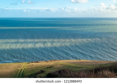 Clouds casting shadows on ripples of the sea