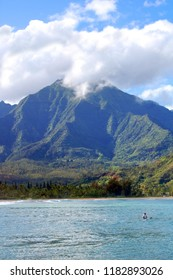 Clouds cover the peak of the Emerald Mountains on the Island of Kauai, Hawaii.  Turquoise waters fill bottom of image and lone surfer sits on Hanalei Bay.