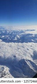 Clouds covering snow peaks of alps mountains